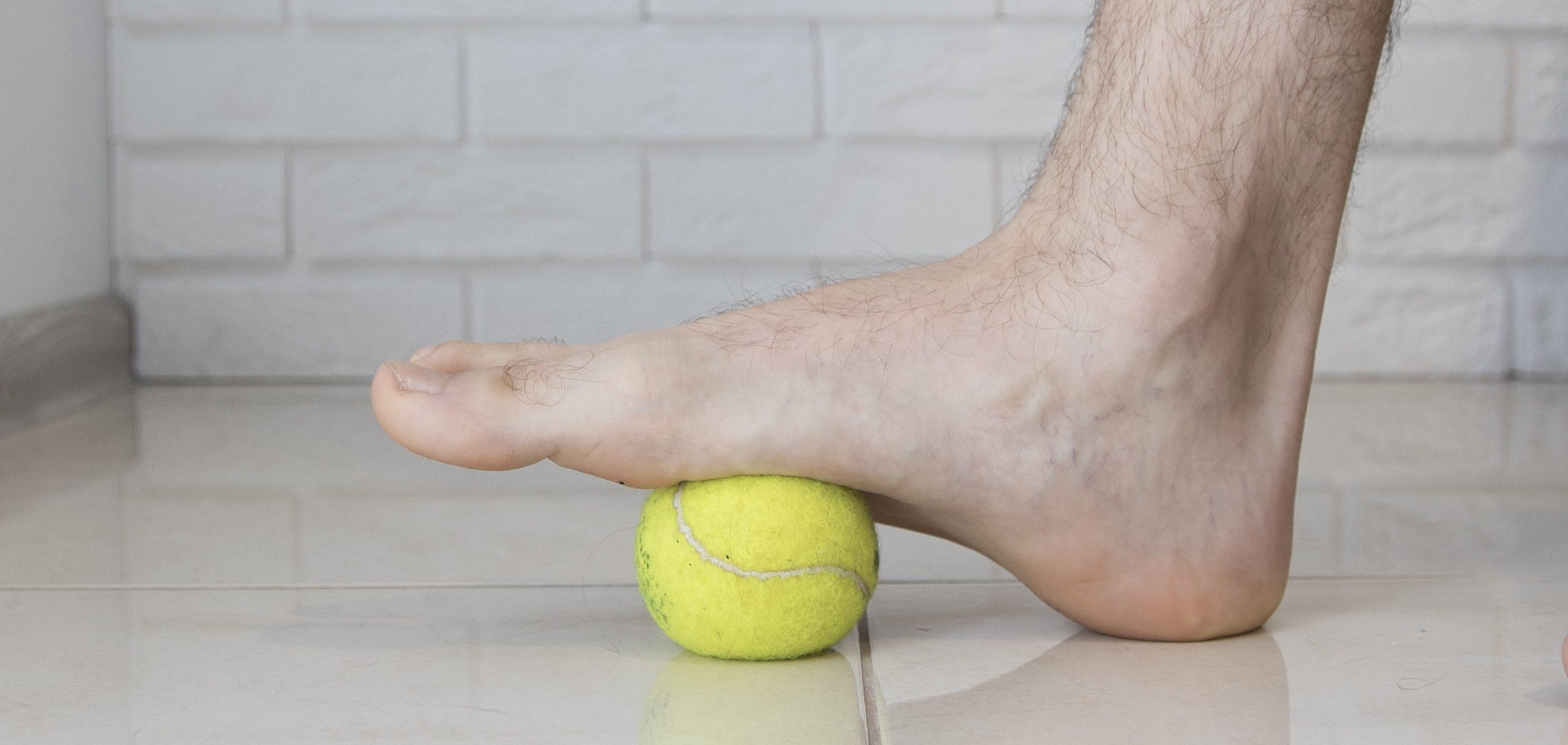 Rolowanie rozcięgna podeszwowego za pomocą piłki tenisowej.